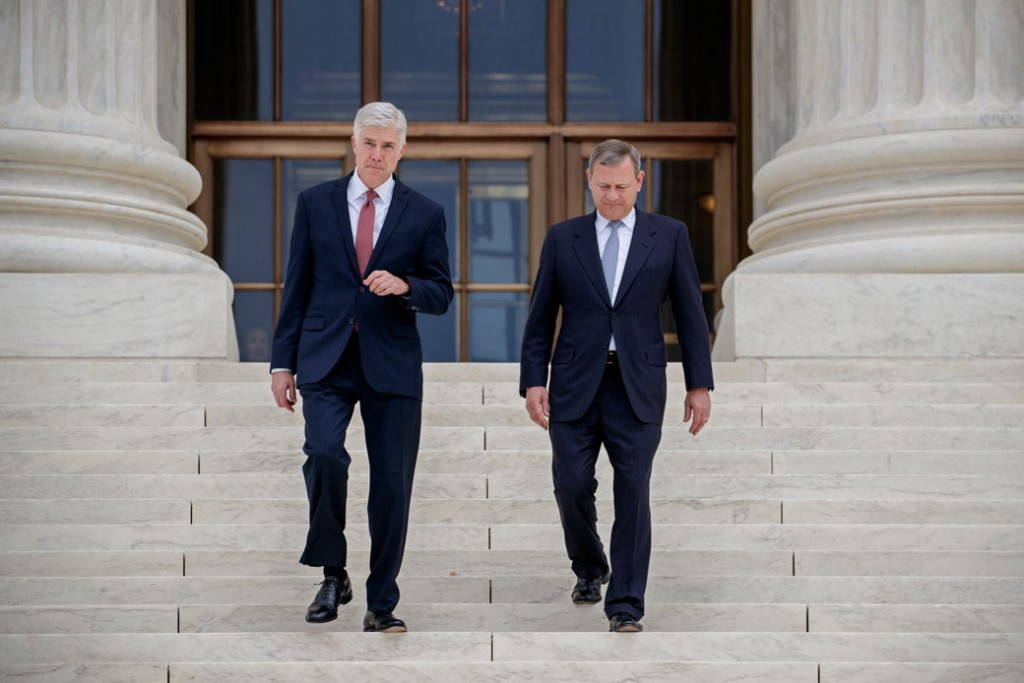 Associate Supreme Court Justice Neil Gorsuch and Chief Justice John Roberts walk down the steps of the Supreme Court in Washington, June 2017.