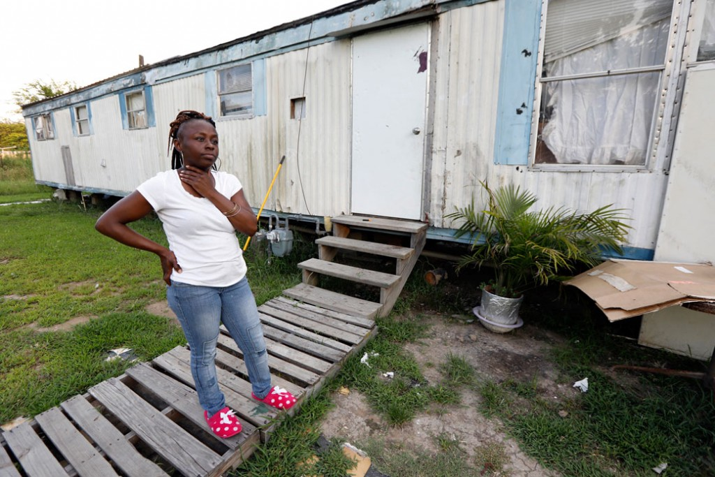 In this July 24, 2017, photograph, Otibehia Allen, a single mother of five, stands outside her rented mobile home in Jonestown, Mississippi. Allen works 30 hours a week as a data entry clerk and transportation dispatcher for a medical clinic, pulling in barely more than minimum wage.