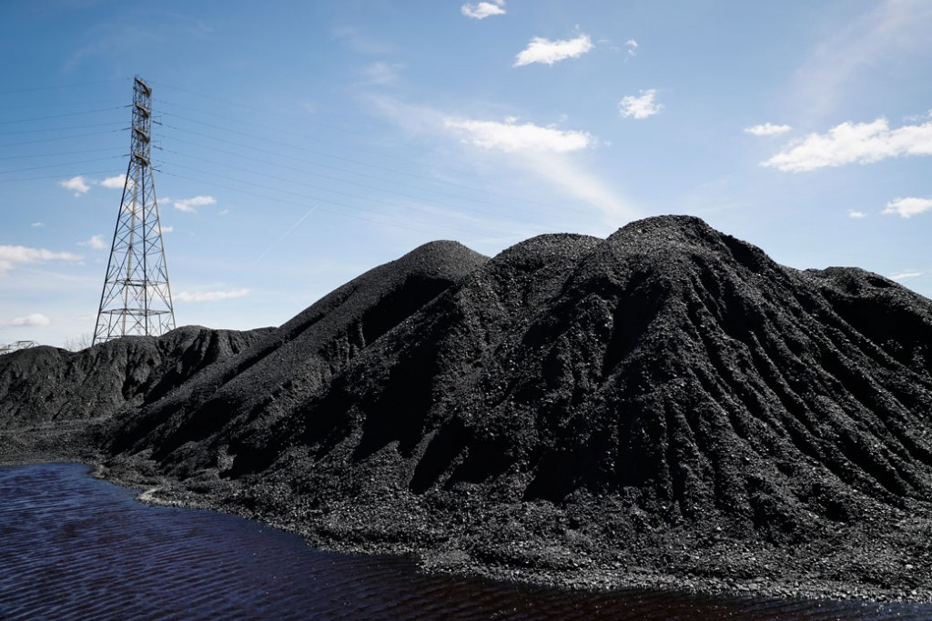 Piles of coal rest at a facility along the Ohio River in Cincinnati, Ohio, as power transmission lines stand in the background, April 7, 2017.