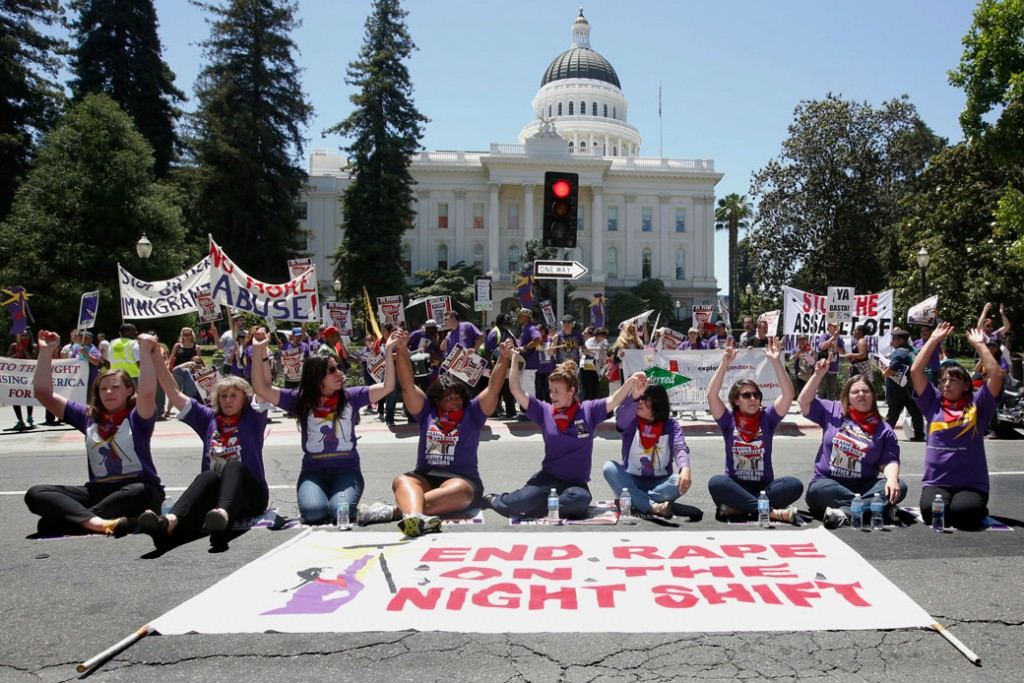 Demonstrators hold hands outside the California State Capitol in Sacramento in support of a measure aimed to protect women custodial workers, May 31, 2016.