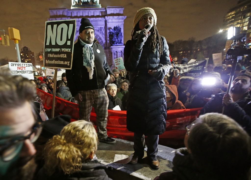 "A woman speaks to demonstrators during what was billed as the second in a series of ""Resist Trump Tuesdays,"" as protesters supporting a multitude of causes gather around to listen, January 31, 2017, at Brooklyn's Grand Army Plaza in New York."