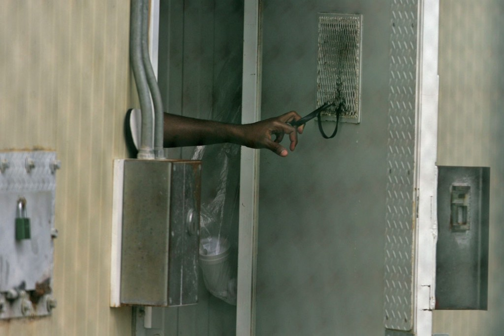 A Guantanamo detainee closes a door at the U.S. detention facility at Guantanamo Bay, Cuba, October 2007.