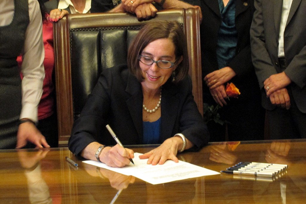 Oregon Gov. Kate Brown (D) signs a bill expanding access to contraception during a ceremony at the state Capitol in Salem, Oregon, on June 11, 2015.
