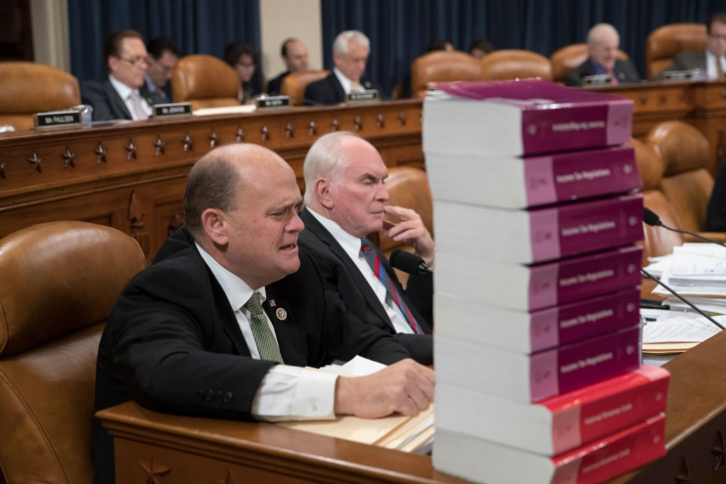 Rep. Tom Reed (R-NY) and Rep. Mike Kelly (R-PA) sit behind a stack of tax volumes on Capitol Hill, November 8, 2017.