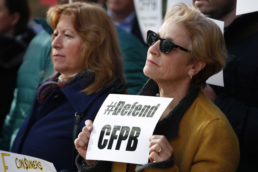 "An advocate, right, holds a sign that says ""Defend CFPB"" outside the Consumer Financial Protection Bureau in Washington, November 27, 2017, during a news conference with consumer groups that oppose Mick Mulvaney being named acting director for the bureau."