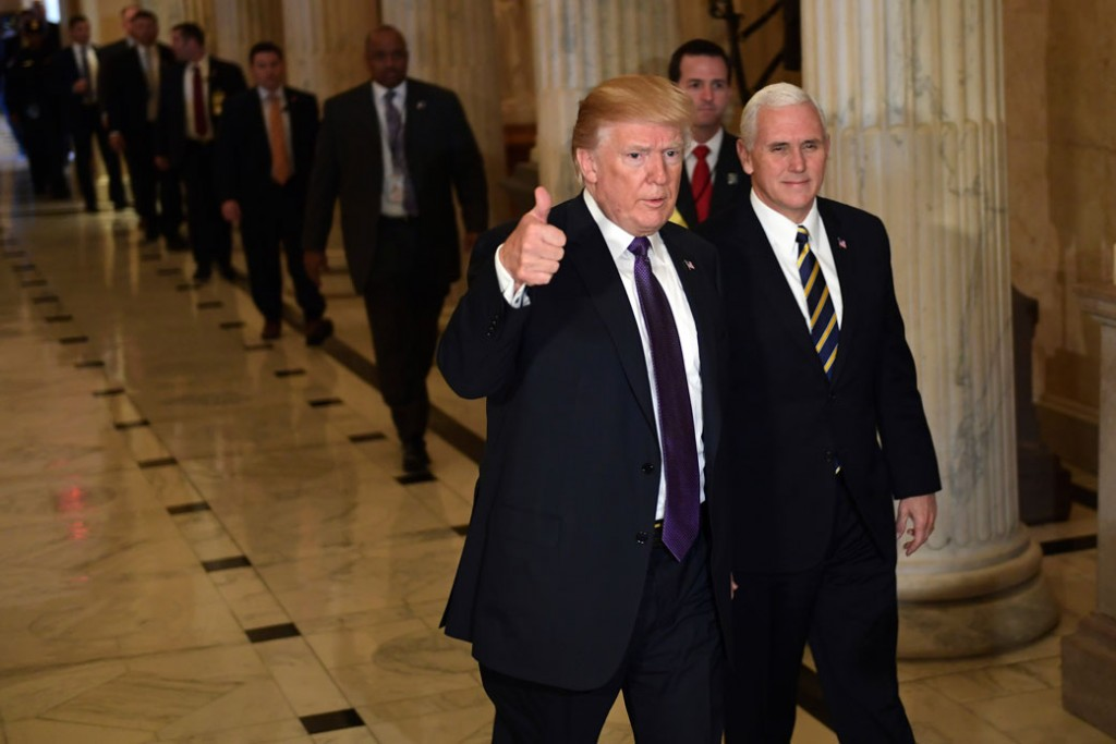 U.S. President Donald Trump gives a thumbs up as he and Vice President Mike Pence depart Capitol Hill in Washington, D.C., November 2017.