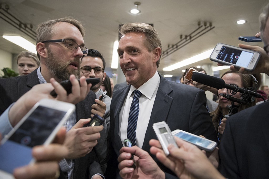 Arizona Sen. Jeff Flake, a member of the Senate Appropriations Committee, takes questions from reporters as he and other lawmakers head to the Senate floor for votes on Capitol Hill in Washington, November 27, 2017.