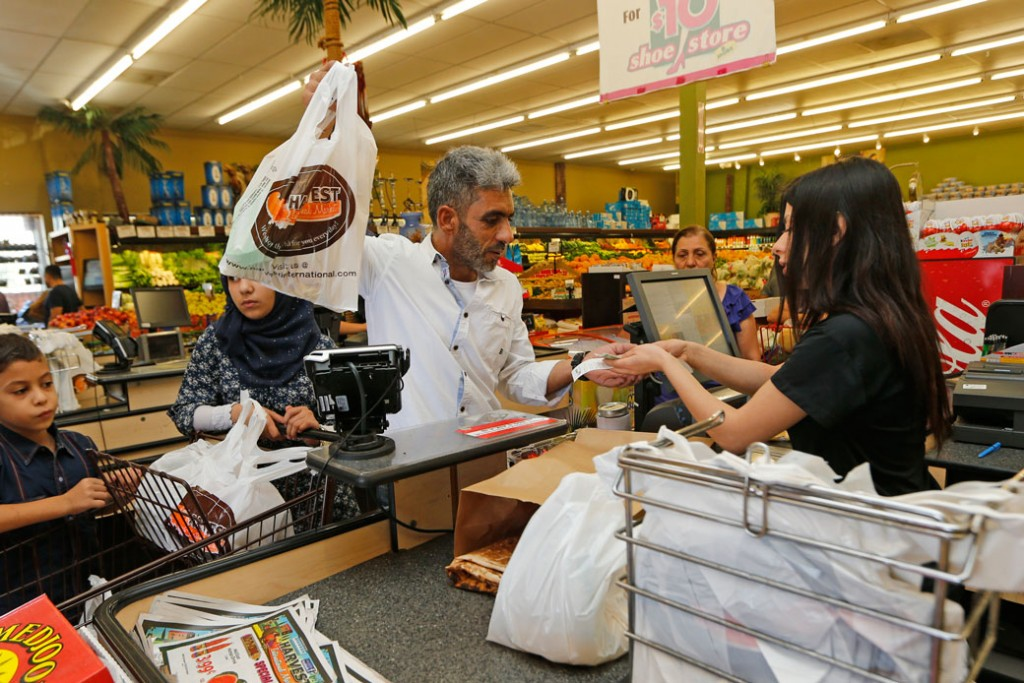 A grocery store cashier checks out a family in El Cajon, California, August 31, 2016.