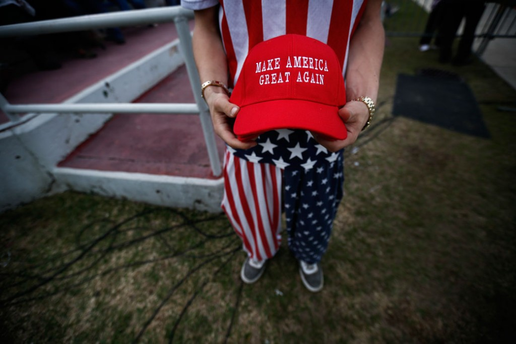 "A man dressed in American flag clothes holds ""Make America Great Again"" hats at a rally for then-President-elect Donald Trump in Mobile, Alabama, December 2016."