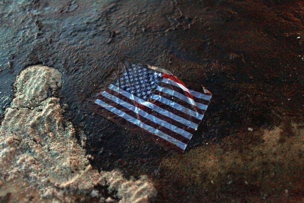An American flag lies in a slick of oil that washed ashore from the Deepwater Horizon oil spill in the Gulf of Mexico on July 4, 2010, in Gulf Shores, Alabama.