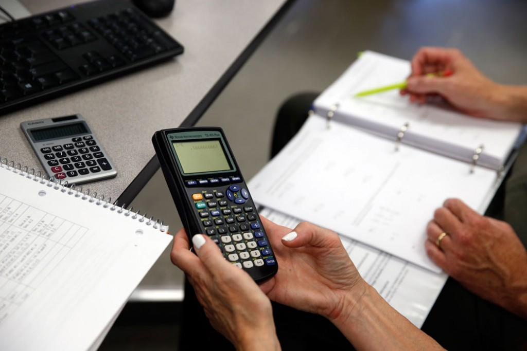 A student uses her calculator during a remedial math class in Haverhill, Massachusetts, June 2015.