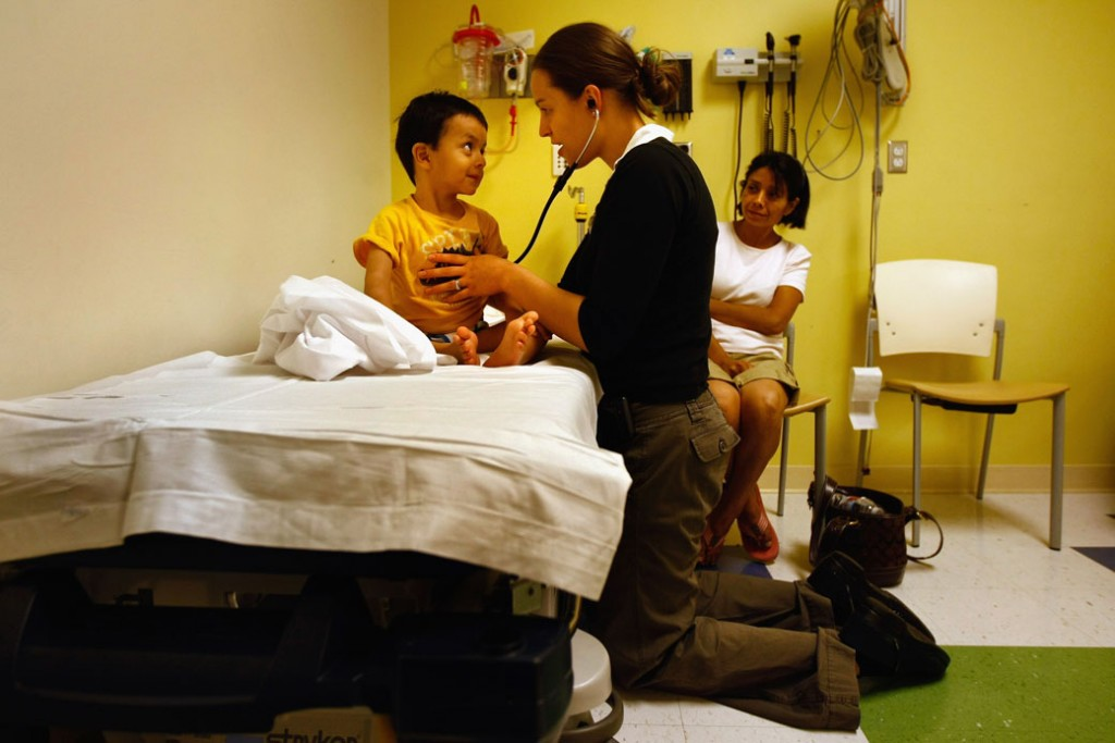 A resident nurse checks the heart rate of a child, September 2009.