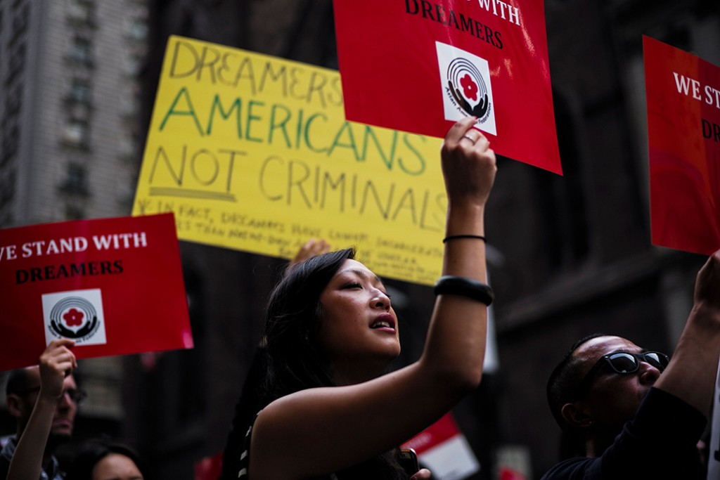 Protesters hold up signs during a rally in support of Deferred Action for Childhood Arrivals, near Trump Tower in New York, October 5, 2017.