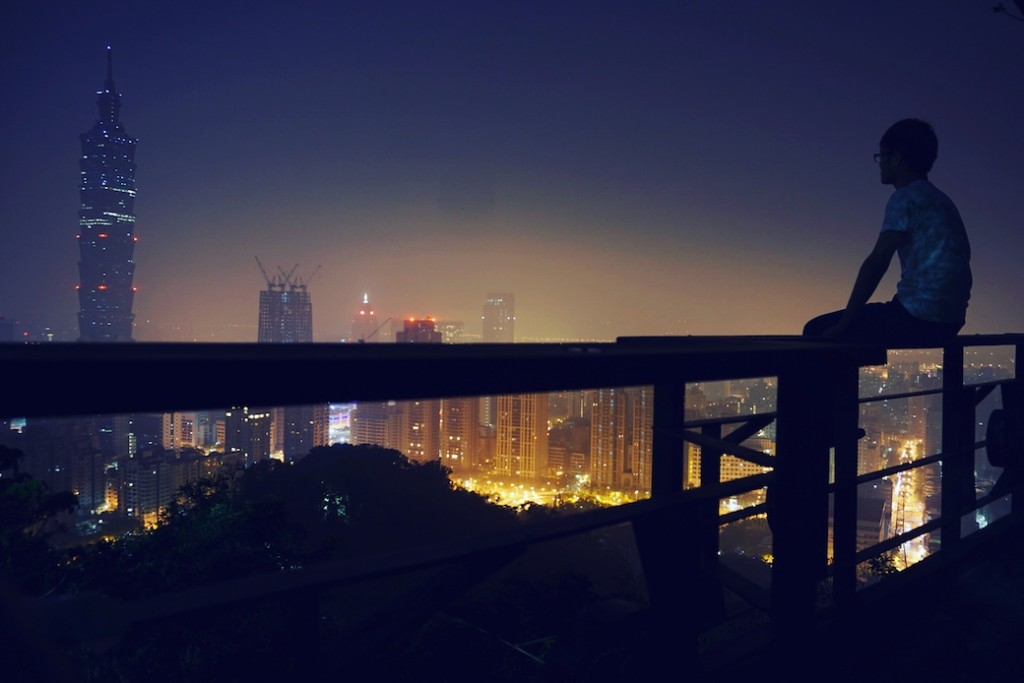 Man Sitting On Balcony Railing Looking At City View