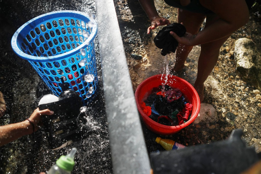 A woman washes clothes with water funneled from a stream nearly one month after Hurricane Maria struck in Utuado, Puerto Rico, October 2017.