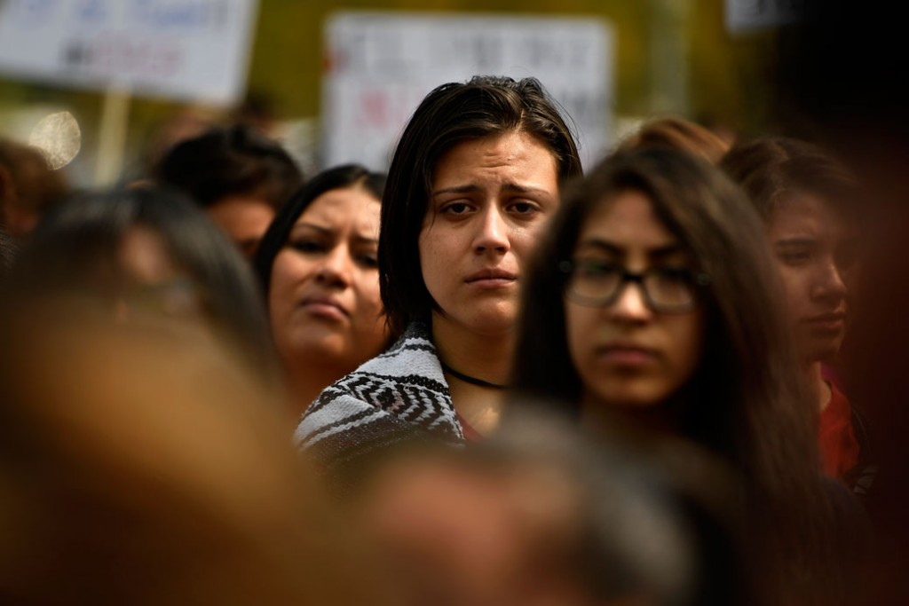 Students listen to stories of parents and families as immigrants and affected individuals march to defend the Deferred Action for Childhood Arrivals (DACA) program in downtown Denver, September 5, 2017.