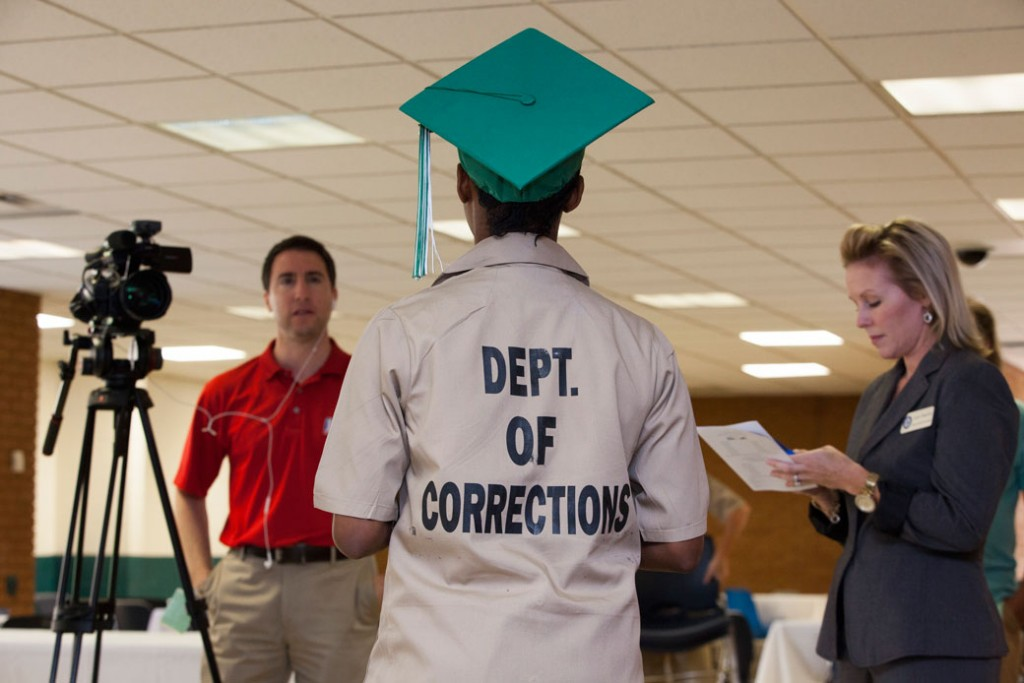 A female inmate who just graduated from high school in prison does an interview for a local TV station in Gainesville, Georgia, July 2015.