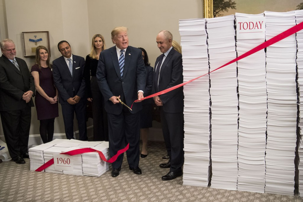 President Donald Trump cuts the ribbon across two stacks of paper symbolizing deregulation at a White House event, Washington, D.C., December 2017.