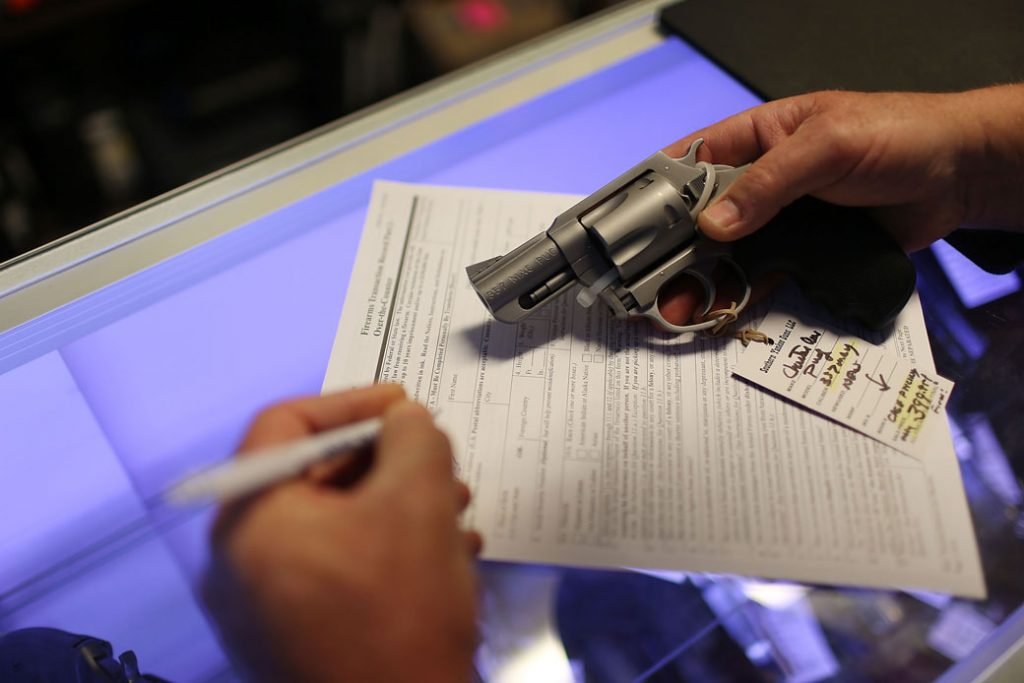 A man in Florida fills out background check paperwork as he purchases a handgun, January 2016.