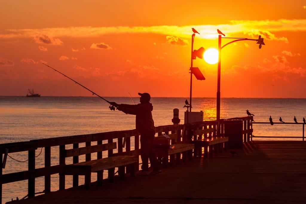 An angler casts from a pier as the sun sets on St. Simons Island, Georgia.