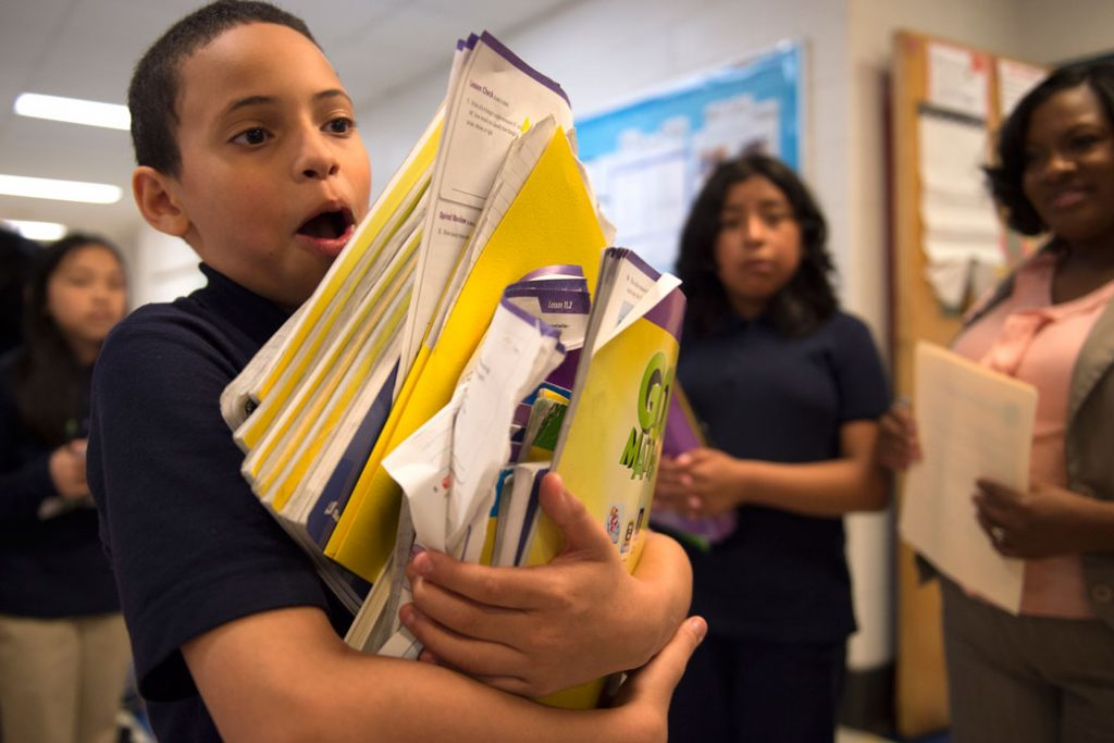 A Philadelphia middle school student carries a stack of books from class, May 2016.