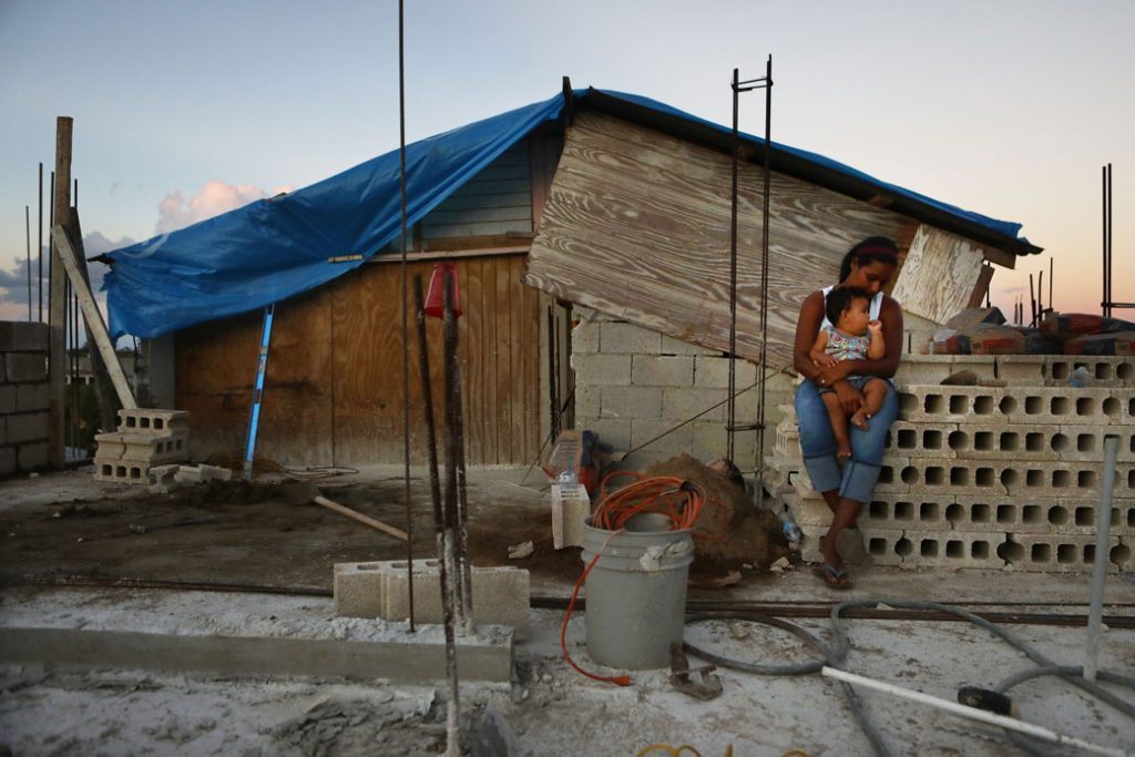 A mother holds her 9-month-old baby at their makeshift home, under reconstruction, after it was mostly destroyed by Hurricane Maria in Puerto Rico, December 2017.