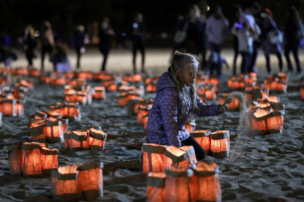 A girl sits among lighted candles during the traditional commemorative ceremony held for domestic violence victims at Chicago's North Avenue Beach, October 2017.