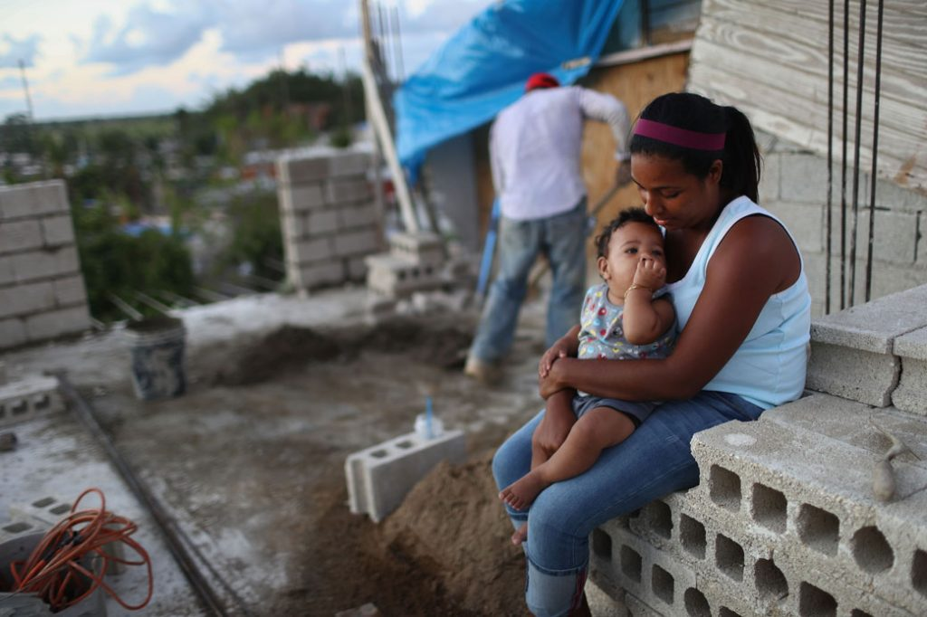 A mother holds her baby as her husband works to reconstruct their home destroyed by Hurricane Maria in San Isidro, Puerto Rico, on December 23, 2017.