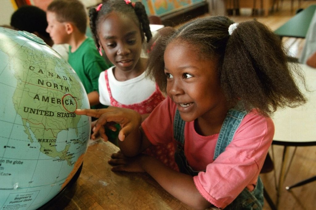 A first-grader in Chicago investigates a circled location on a world globe, August 2000.