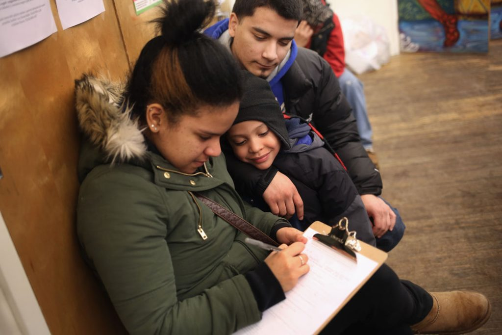 A family fills out an application for DACA at a workshop in New York City, February 2015.