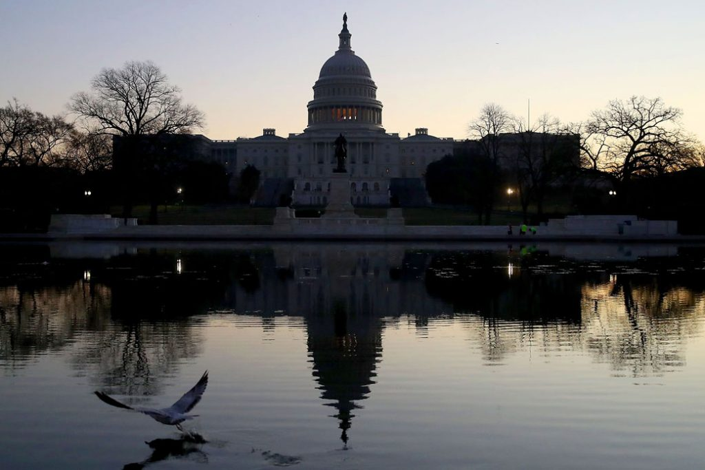 The U.S. Capitol casts early morning reflections on the day that the House and Senate voted on President Donald Trump's tax cut bill, December 19, 2017.