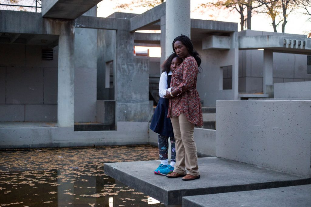 A mother and her daughter stand at a now defunct water fountain in downtown Flint, Michigan, on October 11, 2016.