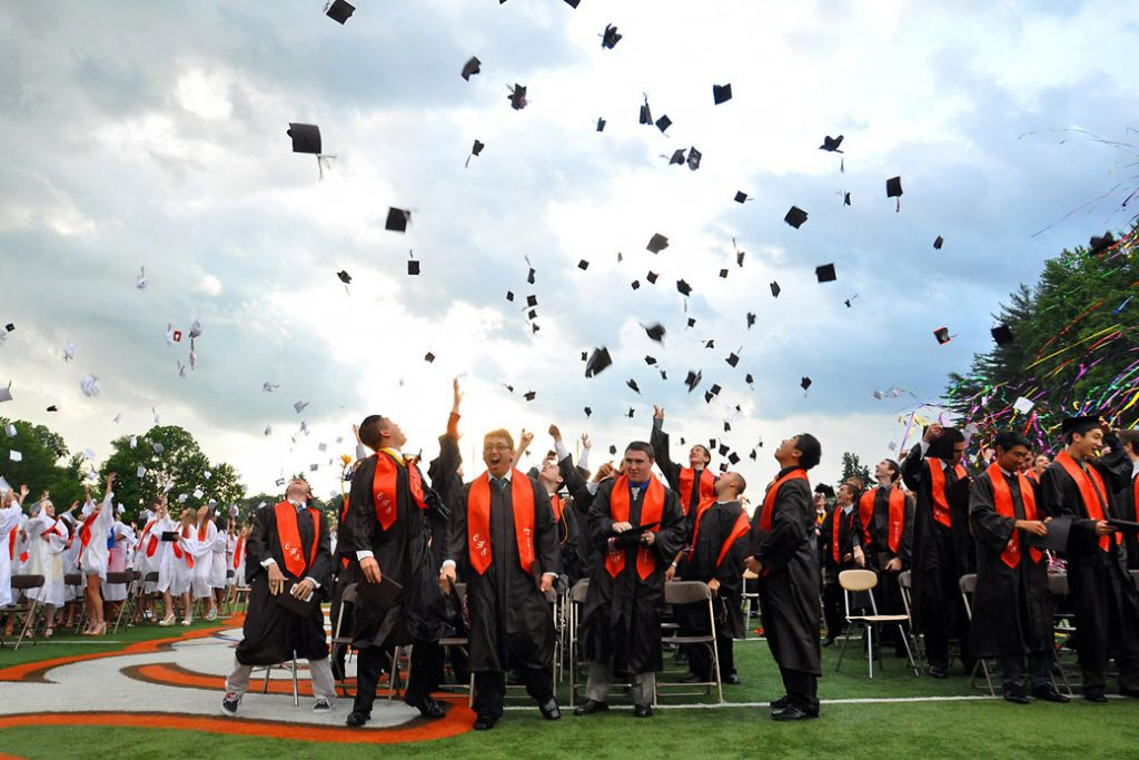 High school graduates throw their caps into the air at the closure of commencement on June 14, 2013.