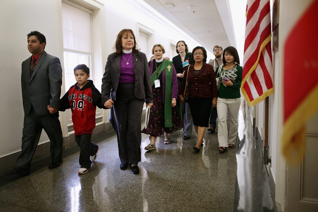 Led by Bishop Minerva Carcaño (third from left), a father and son join people from various Christian denominations at the constituent office of former Speaker of the House John Boehner (R-OH) while lobbying for immigration reform on Capitol Hill, October 8, 2013, in Washington.