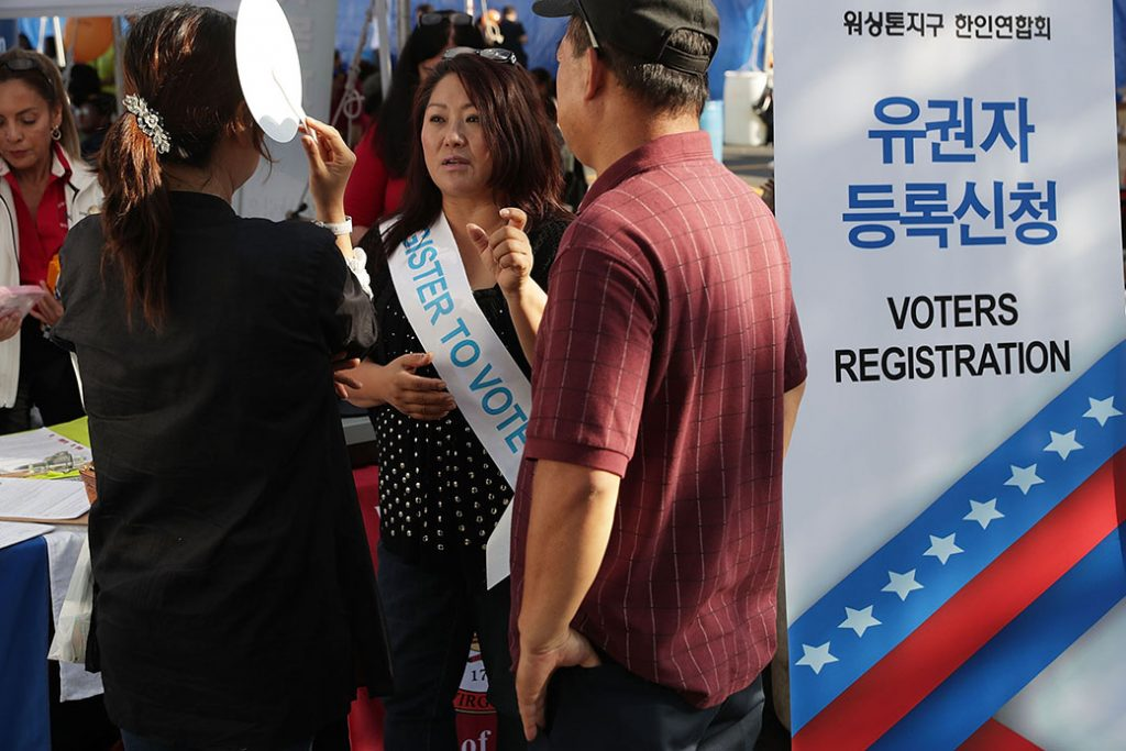 Kelly Lee of the Korean American Association of Washington Metropolitan Area answers questions from a couple as she helps register voters during the annual KORUS festival, a Korean cultural festival, October 2, 2016, in Tysons Corner, Virginia.