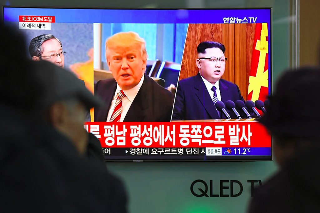 People watch a television news screen showing pictures of U.S. President Donald Trump (center) and North Korean leader Kim Jong Un (right) at a railway station in Seoul, South Korea, November 29, 2017.