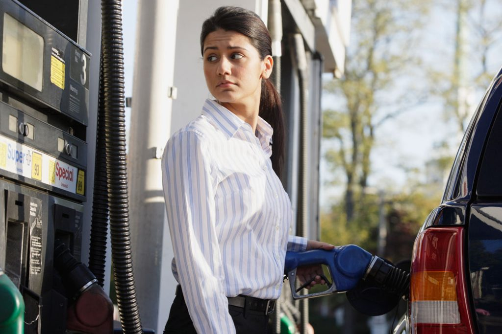 A young woman is seen at a gas pump.