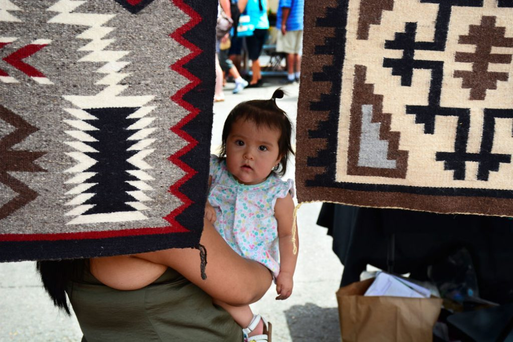 A Navajo mother and weaver holds her Native American daughter in her booth at the Santa Fe Indian Market in Santa Fe, New Mexico.