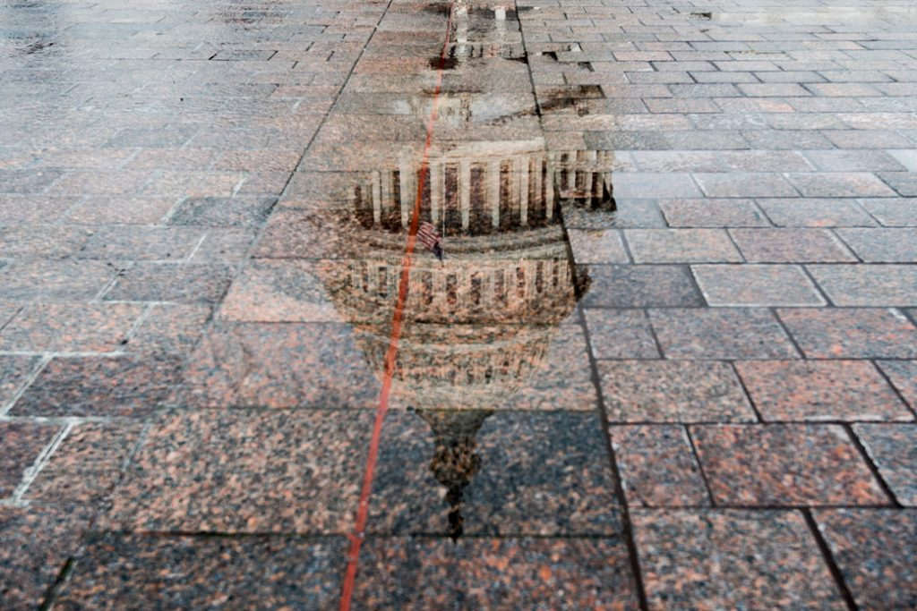 The dome of the U.S. Capitol is reflected in a pool of rainwater, May 2018.
