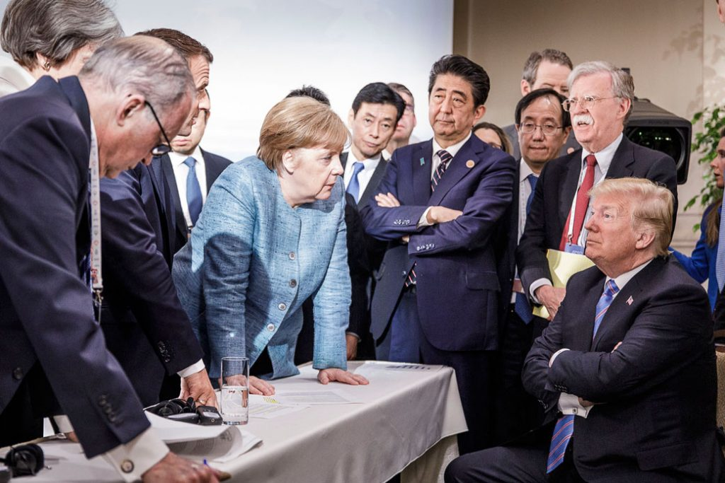 U.S. President Donald Trump deliberates with German Chancellor Angela Merkel and other foreign leaders on the second day of the G-7 summit in Charlevoix, Canada, June 9, 2018.