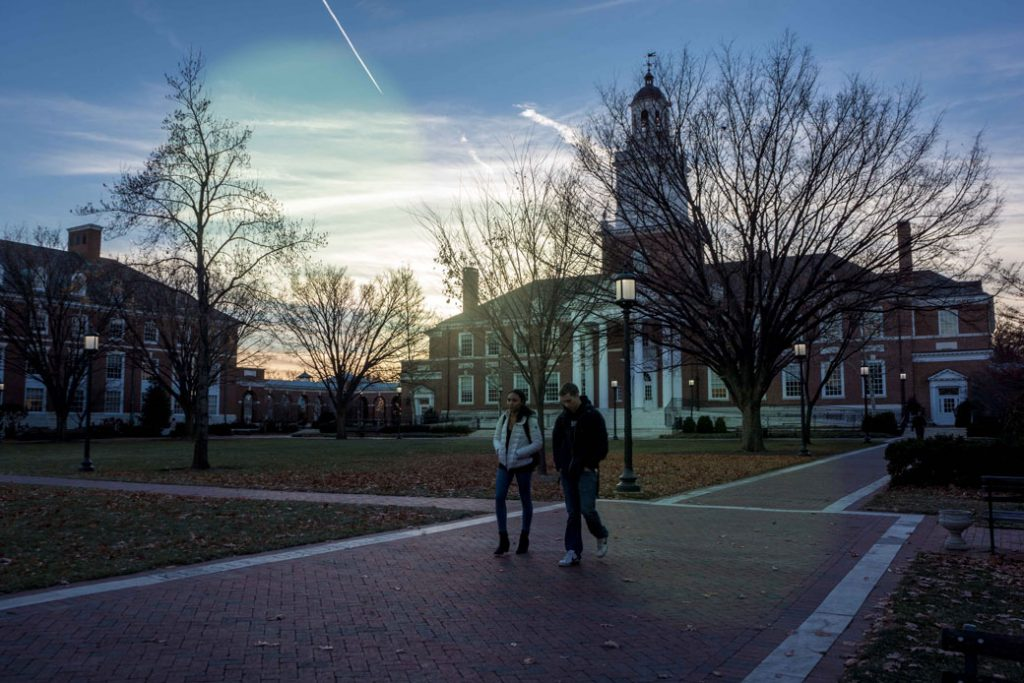 Two students walk on a brick path on a campus, January 2014.