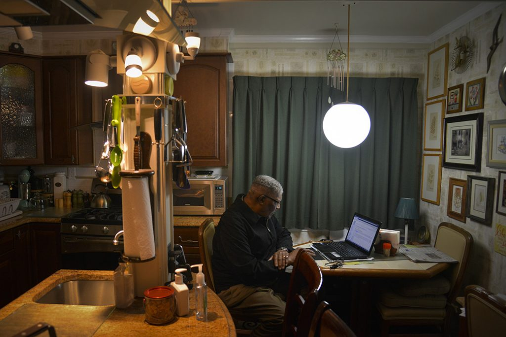 A man reads the news online in his kitchen, May 2014, in Mitchellville, Maryland.