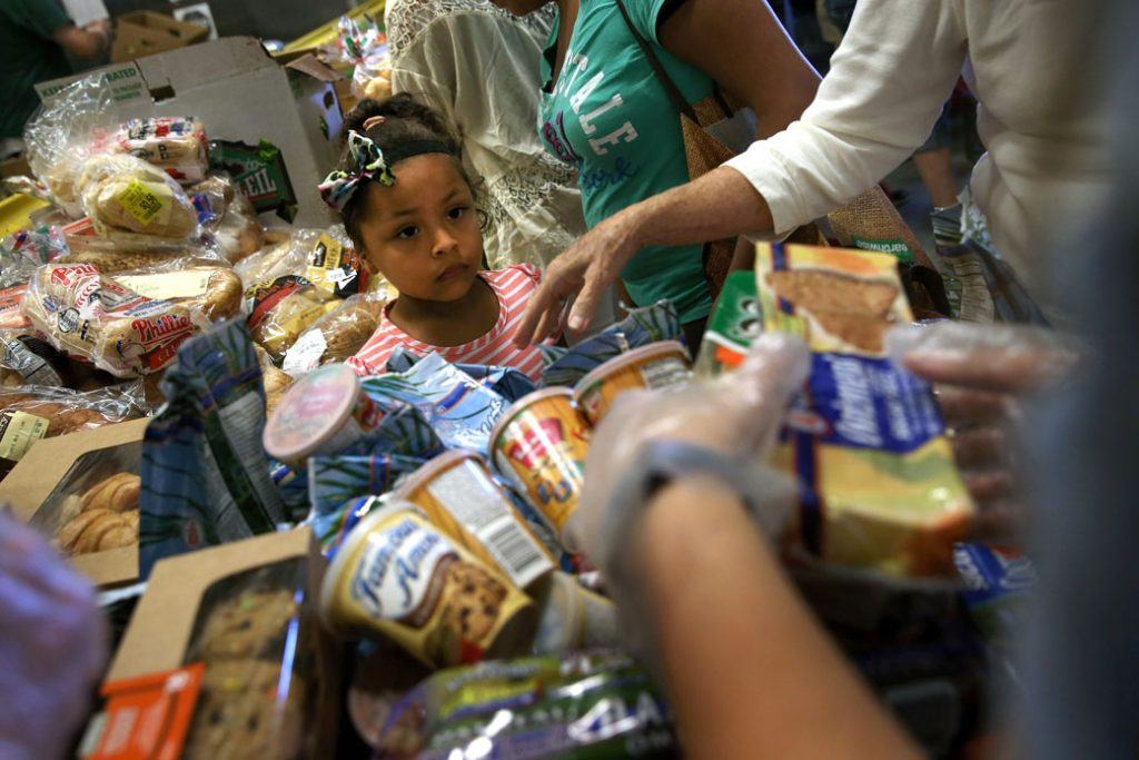 Low-income residents select free bread and produce at the Community FoodBank of New Jersey in Egg Harbor, August 2015.