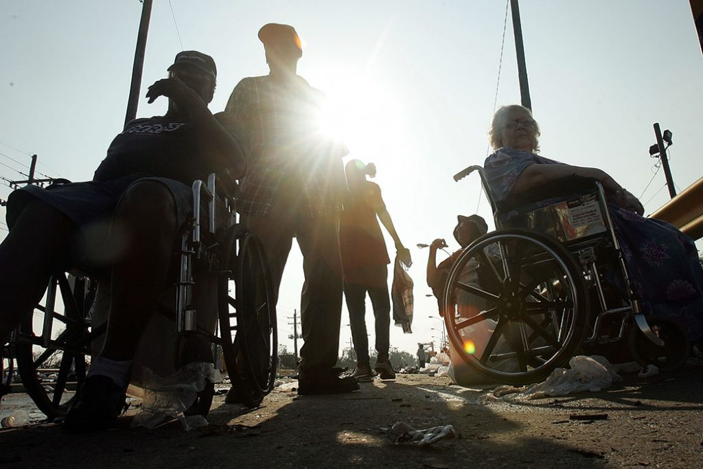 People with disabilities wait for assistance after being rescued from their nursing home, which was inundated by high water from Hurricane Katrina, August 2005, in New Orleans.