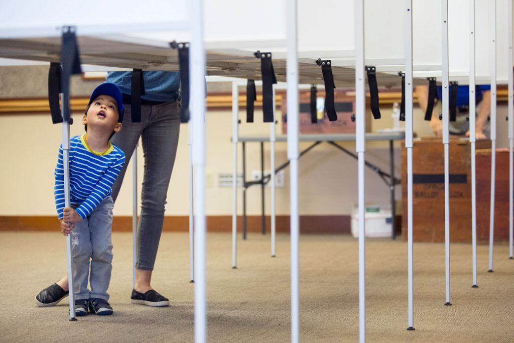 A child peers up into a voting booth as his mother fills out ballots in Scarborough, Maine.