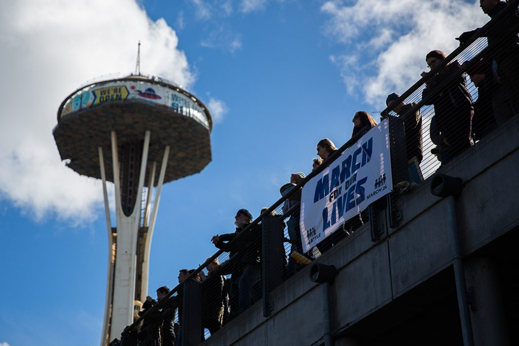 Spectators get a better view of the crowd from Fisher Pavilion, the Space Needle in the background, during the March for Our Lives rally on March 24, 2018, in Seattle, Washington.