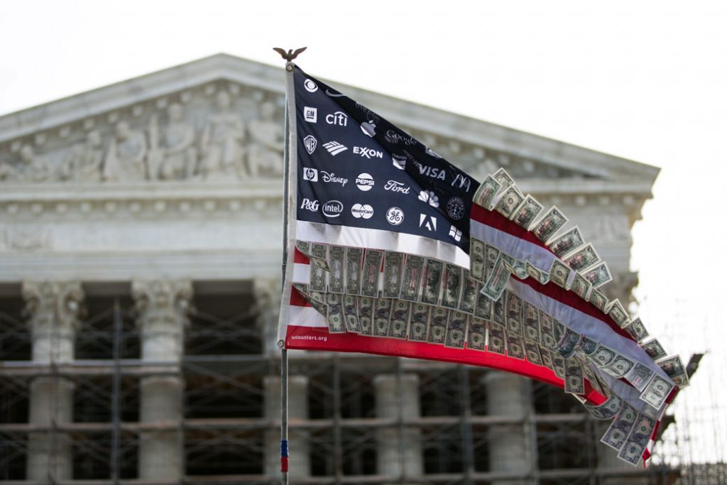 A flag adorned with corporate logos and fake money flies in front of the U.S. Supreme Court in Washington, D.C., October 2013.