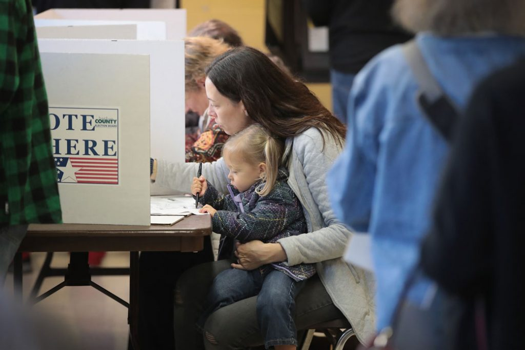 A voter holds her 2-year-old daughter while at a polling place in Kirkwood, Missouri, on November 6, 2018.