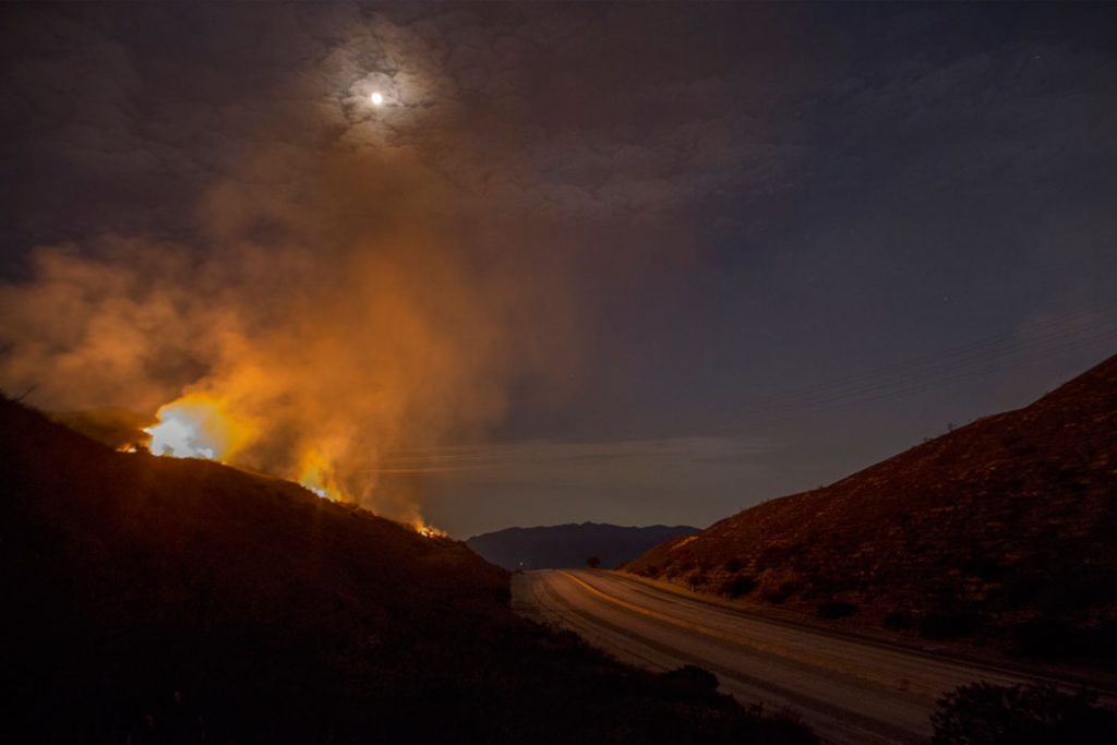 The 210 freeway remains closed as flames continue to spread under moonlight, September 2017.