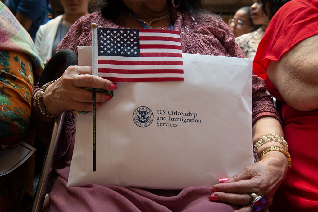 A woman holds the flag and her paperwork as the US Citizenship and Immigration Services welcomes 200 new citizens from 50 countries during a ceremony in honor of Independence Day at the New York Public Library on July 3, 2018 in New York. (Photo by Bryan R. Smith / AFP)        (Photo credit should read BRYAN R. SMITH/AFP/Getty Images)